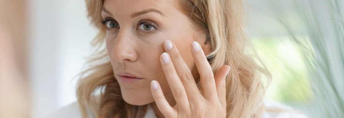 Woman feeling face 4 Laser Therapies for Younger Looking Skin