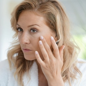 Woman feeling at her skin after treatment The Top 3 Minimally Invasive Skin Procedures