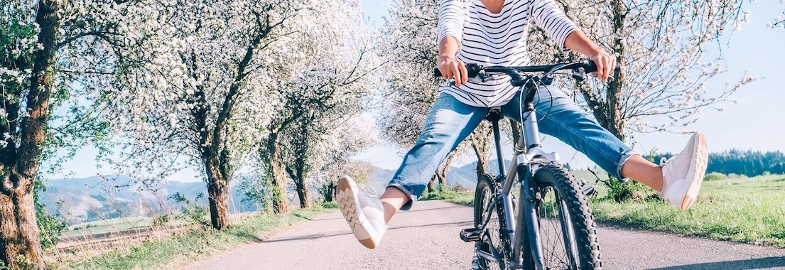 Person riding their bicycle in the spring Springtime and Rashes. How to Enjoy the Sun Without the Rash