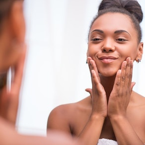 Woman feeling her skin in the mirror The Toll Stress Takes on the Skin
