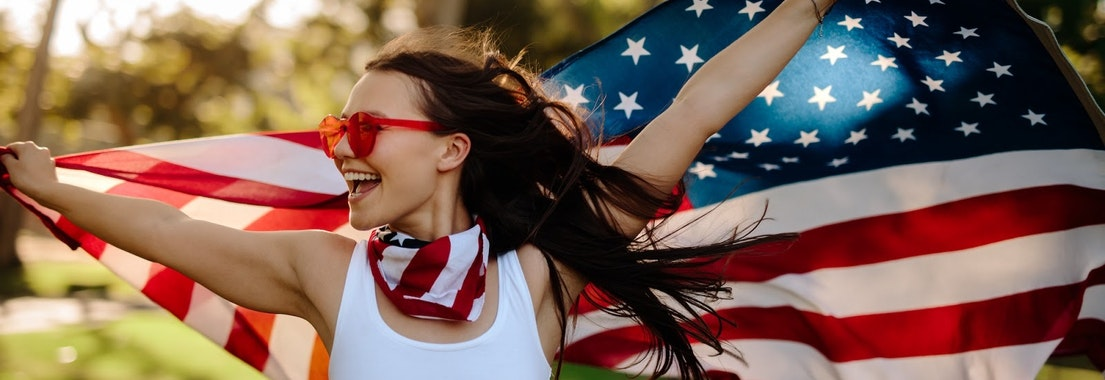 Woman with American flag How to Get the Perfect Glow for Independence Day Without Hurting Your Skin