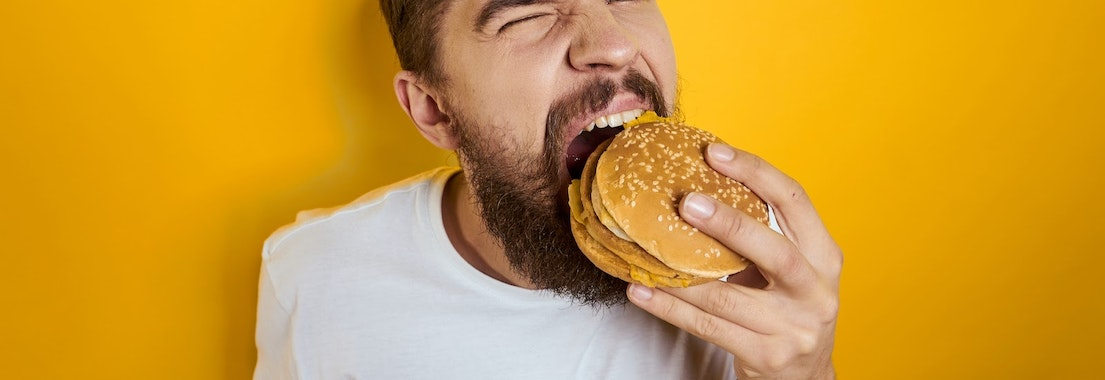Man biting into a hamburger What Processed Meats Can Do to Your Skin