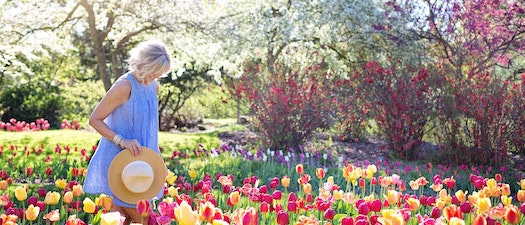Woman watering spring flowers Springtime and Rashes: How to Enjoy the Sun Without the Rash