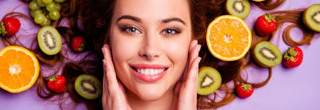 Woman smiling with fruits and vegetables How Eating Fruits and Veggies Rejuvenates Your Skin